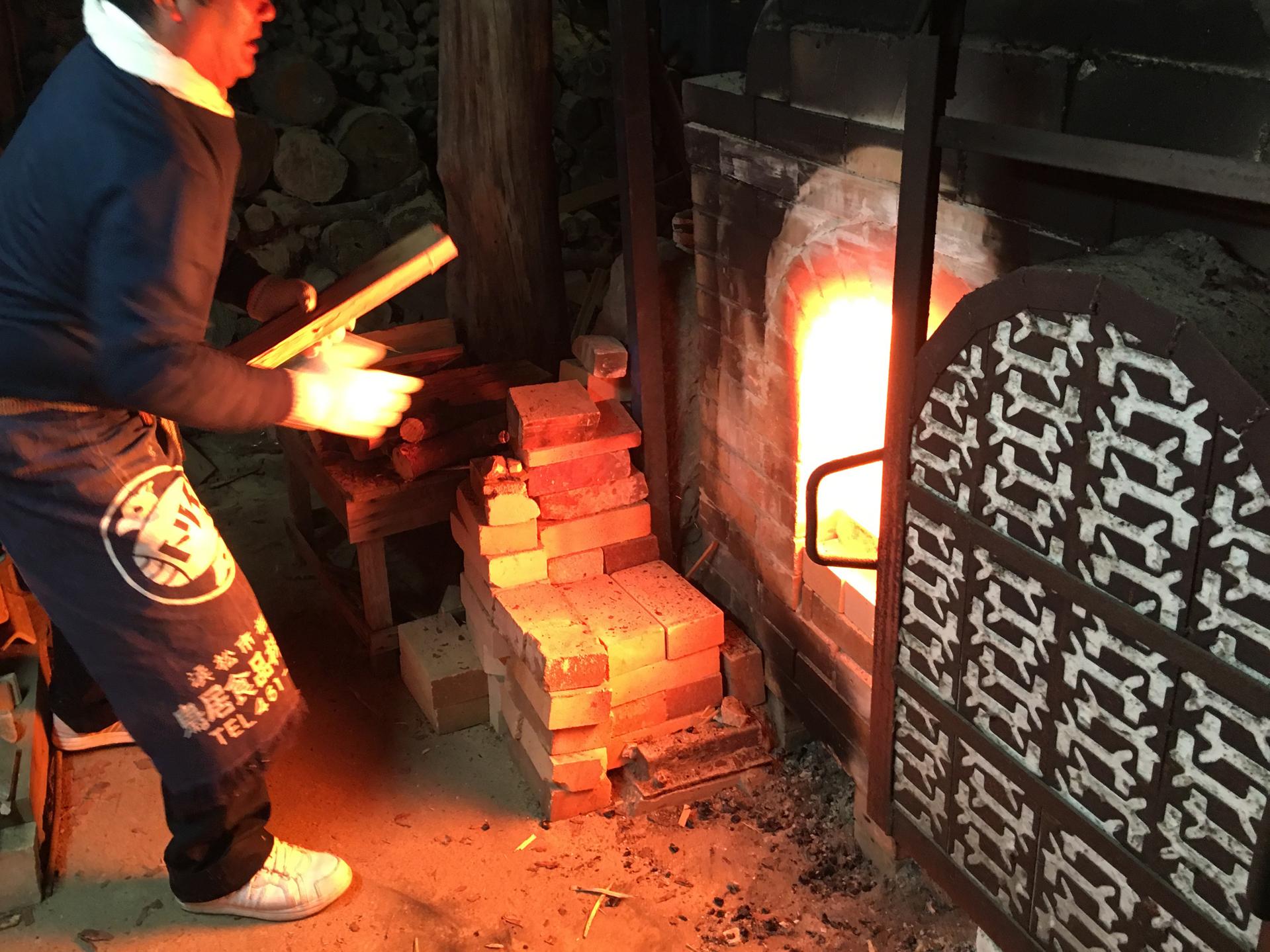 窯に薪を焼べる様子
